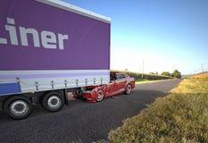 Olycka för två bilar En röd sedan kraschade mot baksidan av en stor lastbil royaltyfri foto