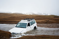 Olycka på vägen, bilkrasch Jeep 4x4 som klibbas i bergflodström Bilen som drunknas i floden Extrem farlig resa Royaltyfri Foto