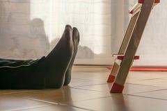 Olyckan i hushållet med en man tittade in stegen royaltyfri bild