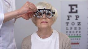 Olycklig åldrig kvinna i refractoren som pressar ögon och skakar huvudet, fel diopter arkivfilmer