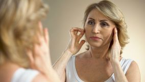 Olycklig åldrig kvinna som ser i den hemmastadda spegeln och att trycka på hennes framsida som åldras process stock video