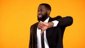 Olycklig afrikansk amerikanman som g?r tummar-ner med avsmak, kundr?tter fotografering för bildbyråer