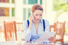 Olycklig allvarlig kvinna som talar på telefoninnehavet som ser dokument Arkivfoton