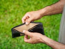 Olycklig bankrutt man med den tomma plånboken Mannen visar hennes tomma vägg Arkivbild
