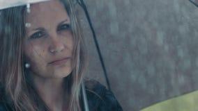 Olycklig blond kvinna med paraplyet under regn stock video