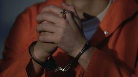 Olycklig Caucasian fånge som ber i cellen som gör tillfredsställelse med synder arkivfilmer