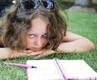Olycklig flicka som ligger på gräset med anteckningsboken Arkivbilder