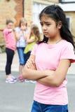 Olycklig flicka som omkring skvallras av skolavänner royaltyfria bilder