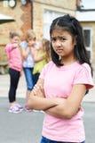 Olycklig flicka som omkring skvallras av skolavänner royaltyfri bild