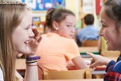Olycklig flicka som omkring skvallras av skolavänner i klassrum royaltyfri fotografi
