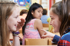 Olycklig flicka som omkring skvallras av skolavänner i klassrum arkivbild