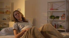 Olycklig gravid kvinna som tuggar munken som ligger i säng, lynnegungor som äter för mycket stock video