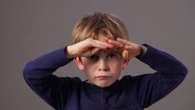 Olycklig härlig ung pojke som rynkar pannan, i att se bort eller framåt stock video