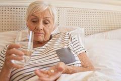 Olycklig hög kvinna som ligger i säng som tar medicin royaltyfri foto