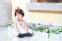 Olycklig kines behandla som ett barn flickablickar på bubblor i en trädgård Royaltyfri Bild