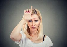 Olycklig kvinna för stående som ger förloraretecknet på pannan och att se dig med ilska och hat på framsida royaltyfri bild