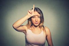 Olycklig kvinna som ger förloraretecknet på pannan som ser dig, avsmak på framsida arkivfoton