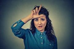 Olycklig kvinna som ger förloraretecknet på pannan som ser dig, avsmak på framsida Royaltyfri Fotografi