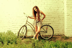 Olycklig kvinna som poserar mot den vita väggen med hennes stads- cykel, mycket utrymme för text, kors-bearbetad färgförskjutning Royaltyfri Foto