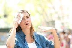 Olycklig kvinna som svettas lida en v?rmeslagl?ngd royaltyfri fotografi