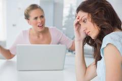 Olycklig kvinna som tänker, medan hennes vän förhör henne arkivfoton