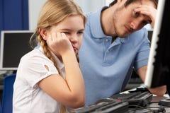 Olycklig lärare och flicka som använder datoren i grupp Arkivbild