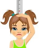 Olycklig liten flicka som mäter hennes tillväxt i höjd Arkivbild
