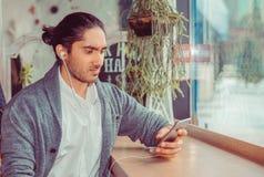 Olycklig man med hörlurar som ser till en mobiltelefon arkivfoton
