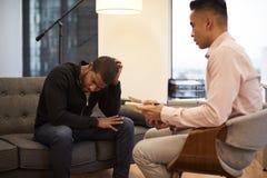 Olycklig man som i regeringsställning sitter på soffamöte med den manliga rådgivaren arkivbilder