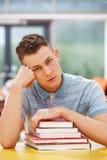 Olycklig manlig student Studying In Classroom med böcker Royaltyfri Fotografi