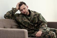 Olycklig och ledsen soldat i den gröna moro likformign med krigsyndrom fotografering för bildbyråer