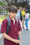 Olycklig pojke som omkring skvallras av skolavänner royaltyfria bilder