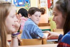 Olycklig pojke som omkring skvallras av skolavänner i klassrum royaltyfri bild