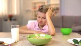 Olycklig pojke som ser havremj?let med avsmak, osmaklig mat, sund frukost royaltyfri fotografi
