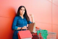 Olycklig shopparekvinna med shoppingvagnen framme av lagret arkivfoto