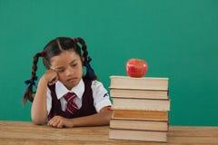 Olycklig skolflicka som ser det bokbunten och äpplet mot den svart tavlan Royaltyfria Bilder