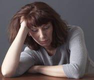 Olycklig 50-talkvinna som tänker om att åldras frågor Royaltyfria Foton