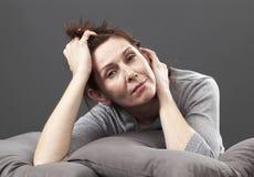 Olycklig 50-talkvinna som tänker om att åldras frågor Royaltyfri Bild