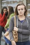 Olycklig tonårs- flicka som omkring skvallras av jämliken Royaltyfria Foton