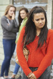 Olycklig tonårs- flicka som omkring skvallras av jämliken Arkivfoto