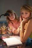 Olycklig tonårs- flicka som ser dagboken i sovrum på natten Arkivfoton