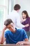 Olycklig tonårs- pojke med föräldrar som argumenterar i bakgrund royaltyfri bild