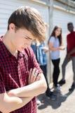 Olycklig tonårs- pojke som omkring skvallras av jämliken royaltyfri fotografi