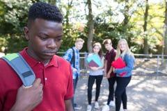 Olycklig tonårs- pojke som omkring skvallras av skolavänner royaltyfri bild
