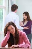 Olycklig tonårs- flicka med föräldrar som argumenterar i bakgrund Royaltyfria Bilder