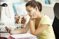 Olycklig tonårs- flicka som studerar på skrivbordet i sovrummet som ser mobiltelefonen Arkivfoton