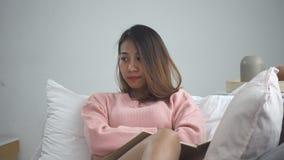 Olycklig ung asiatisk kvinna studera hemmastadd läsning sms eller textmeddelande på hennes mobiltelefon med att ligga på soffan h arkivfilmer