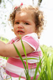 Olycklig ung flicka som sitter i sommarfält Arkivbild