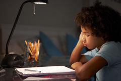 Olycklig ung pojke som studerar på skrivbordet i sovrum i afton Arkivbild