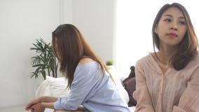 Olyckliga asiatiska lesbiska lgbtpar som sitter varje sida av soffan med lynnig sinnesrörelse i vardagsrum stock video